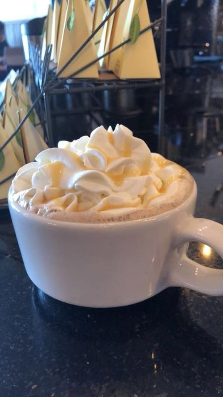 A large white mug with whip cream on top of coffee.