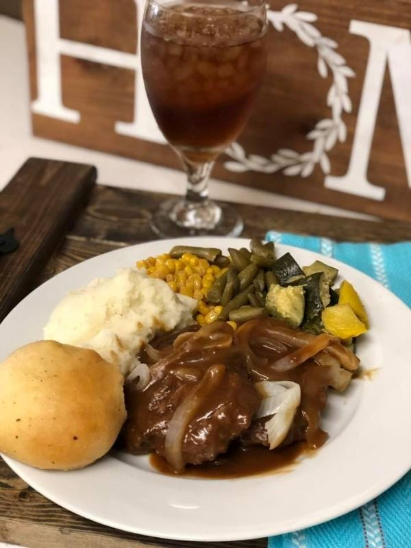 Vela Farms famous hamburger steak with brown gravy, seasoned squash, mash potato and homemade roll.