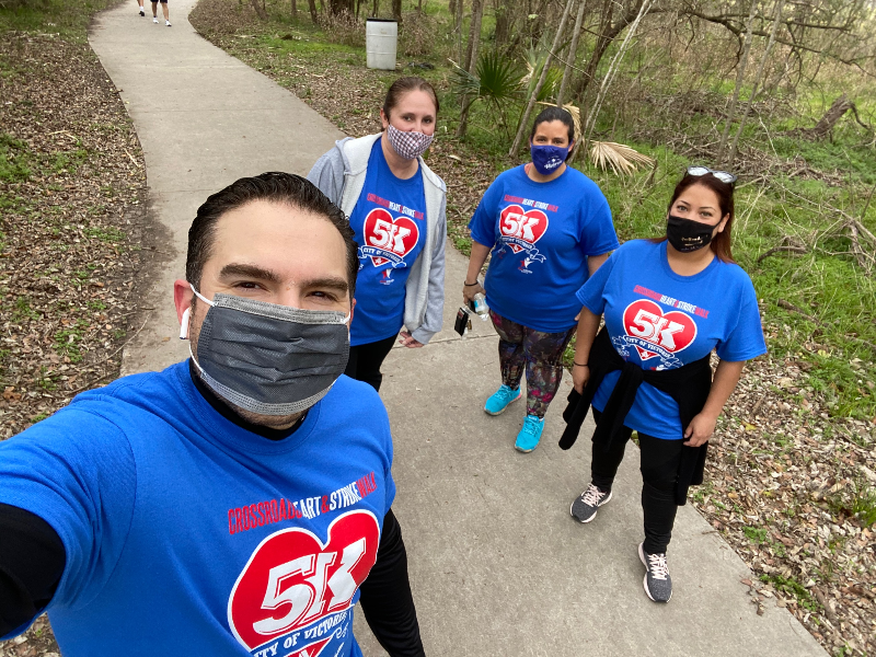 Jesús Garza and 3 City employees on walking trail in Riverside Park wearing masks & matching shirts