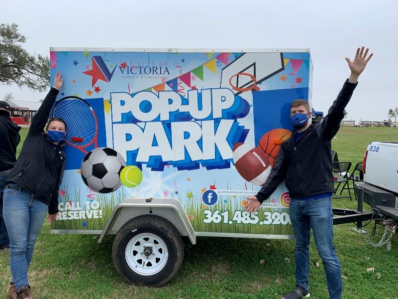 "Masked woman and man pose with arms outstretched by small pull-trailer labeled ""pop-up park"""