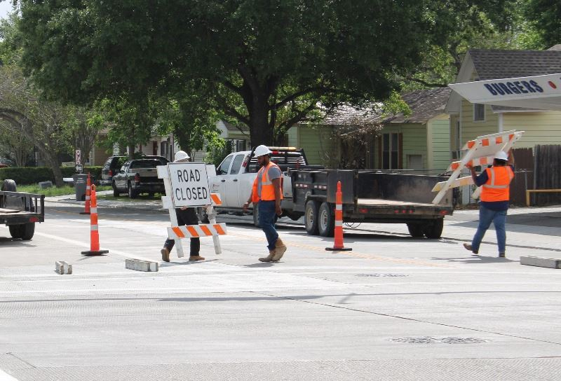 Construction workers move orange-and-white barricades from Crestwood near Dairy Treet