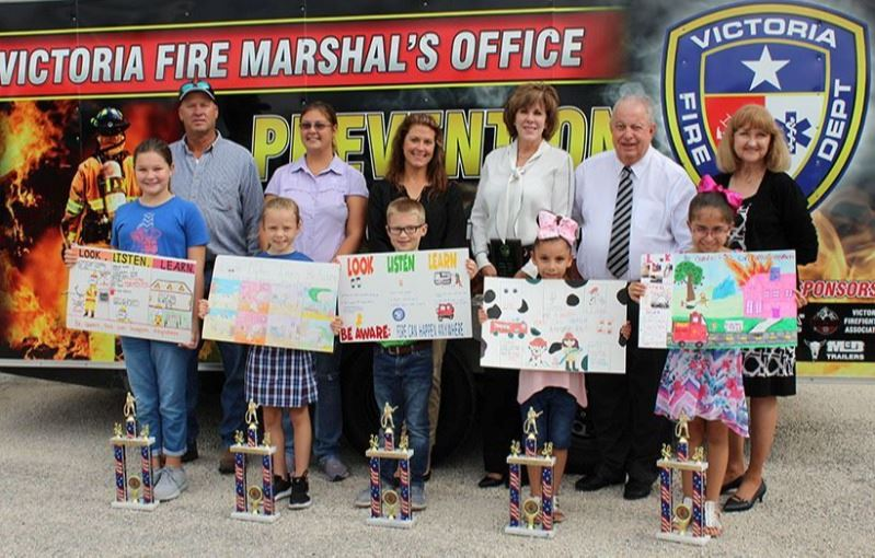 Fire prevention week with students showing off trophies